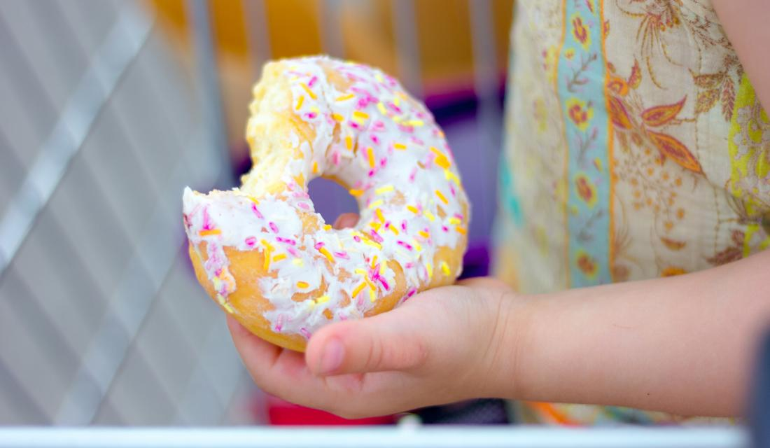 Angebissener Donut in Kinderhand